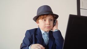 Little boy calling by mobile phone front laptop in business office. Young businessman talking by smartphone while. Business conversation at workplace in office stock video footage
