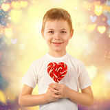 Little boy with candy red lollipop in heart shape. Valentine`s day art portrait. Stock Image