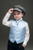 Little boy in cap and blue vest Stock Photography