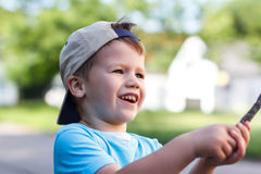 Little boy in cap with bracnch Stock Photo