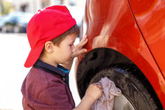 Little boy in cap cleaning red car wheel Stock Photo