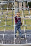 Little boy in cap climb on jungle gym at park.  royalty free stock photos