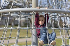 Little boy in cap climb on jungle gym at park.  stock photography