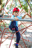 Little boy in cap climb on jungle gym Stock Image