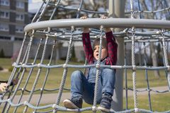 Little boy in cap climb on jungle gym at park.  stock photos