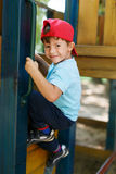 Little boy in cap climb up Stock Photos