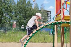 Little boy in cap climbs. On children playground at summer sunny day Royalty Free Stock Image