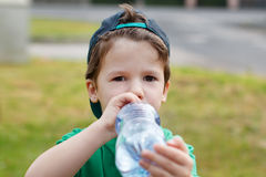 Little boy in cap drink water Stock Images