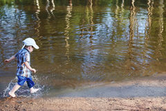 Little boy in cap and goes in water of pond Stock Images