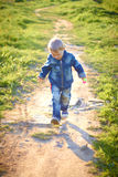 Little boy in cap playing outdoors in summer on a Sunny warm day, grass, greens, nature Stock Photos