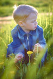 Little boy in cap playing outdoors in summer on a Sunny warm day, grass, greens, nature Royalty Free Stock Image