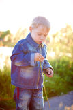 Little boy in cap playing outdoors in summer on a Sunny warm day, grass, greens, nature royalty free stock photography