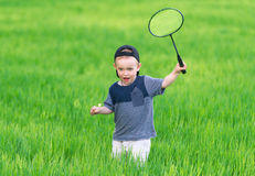The little boy in cap plays in grass. Royalty Free Stock Photos