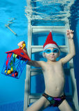 A little boy in a cap Santa Claus with a gift in hand sits underwater on the stairs at the bottom of the pool. The view from under the water. Close-up Stock Photography