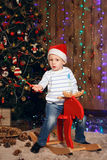 Little boy in a cap of Santa Claus riding a reindeer toy Royalty Free Stock Photography