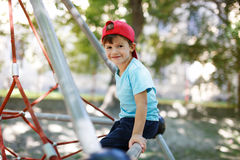 Little boy in cap sit on jungle gym Royalty Free Stock Photos