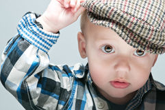 Little boy in a cap sits at the table Stock Photos