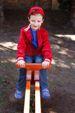 Little boy in cap sitting on seesaw Stock Photo