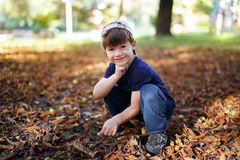 Little boy with cap squat in nature Stock Photography