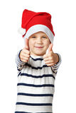 Little Boy in cappello di Santa con i pollici sull'approvazione del segno isolati Fotografie Stock