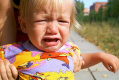 The little boy is capricious. Portrait of the crying kid in the summer in the street Royalty Free Stock Images
