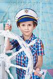 Little boy captain with steering wheel on ship Stock Image