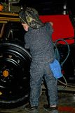 Little boy in a car mechanic uniform working on a tire. Little boy in an auto garage mechanic uniform with hat on backwards royalty free stock image