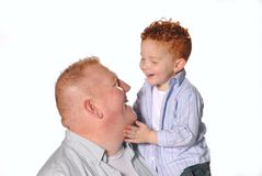 Little Boy Caressing Dad's Face. Little redheaded boy laughing and caressing his father's face Royalty Free Stock Photo