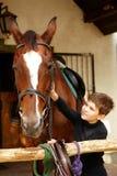 Little boy caressing horse stock image