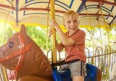 Little Boy on a Carnival Carousel Stock Image