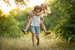 Little boy carries girl on his back. Royalty Free Stock Photography
