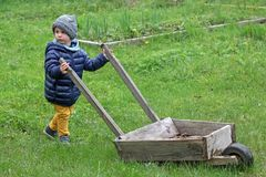 Little boy carries a large wooden wheelbarrow on the grass. Child in the country in the spring in warm clothes. royalty free stock images