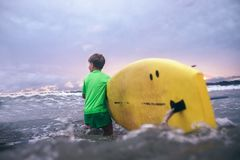 Little boy carries yellow surf board into ocean waves. Surfing First steps concept stock photography