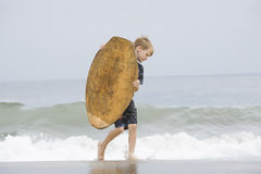 Little Boy Carrying Bodyboard In Sea Stock Image