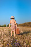 Little boy carrying heavy suitcase in wheat field Stock Image
