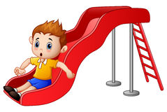 Little boy cartoon playing on a slide royalty free illustration