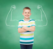 Little boy in casual clothes with arms crossed. Happiness, childhood, school, education and people concept - smiling little boy in casual clothes over green royalty free stock images