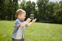 Little Boy Catch Soap Bubbles Stock Photo