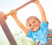 Little boy catch up on the horizontal  bar Stock Photography