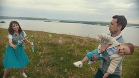 Little boy catches bubbles and rejoices in the hands of his father, cloudy. Telephoto shot stock video footage