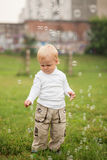 Little  boy catches soap bubbles Royalty Free Stock Images