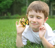 Little Boy Catching Spring Butterfly Outside. A little boy is outside in the spring catching a yellow butterfly on green grass for a nature concept Royalty Free Stock Photos