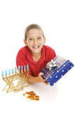 Little Boy Celebrates Hanukkah. Cute Jewish boy with his Chanukah menorah, gift, and a dreidel and chocolate gelt coins. White background stock photo