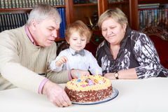 Little boy celebrating his birthday at home with his grandparent Royalty Free Stock Photo