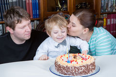 Little boy celebrating his birthday at home with his parents Royalty Free Stock Images