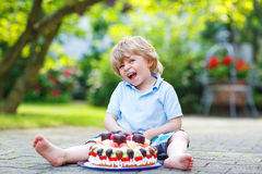 Little boy celebrating his birthday in home's garden with big ca Royalty Free Stock Photography