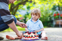Little boy celebrating his birthday in home's garden with big ca Royalty Free Stock Image