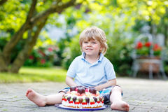 Little boy celebrating his birthday in home's garden with big ca Stock Photography
