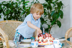 Little boy celebrating his birthday in home's garden with big ca Stock Images
