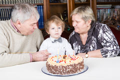 Little boy celebrating his birthday at home with his grandparent Royalty Free Stock Photography